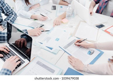 Business team meeting in the office and discussing financial strategies, they are checking reports and paperwork, unrecognizable people