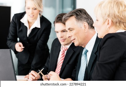 Business - team meeting in an office with laptop, the boss with his employees looking at good news or numbers on laptop computer
