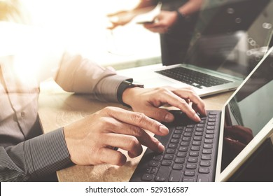 Business team meeting present. Photo professional investor working with new start up project. Digital tablet laptop computer design smart phone using, keyboard docking screen foreground,sun flare