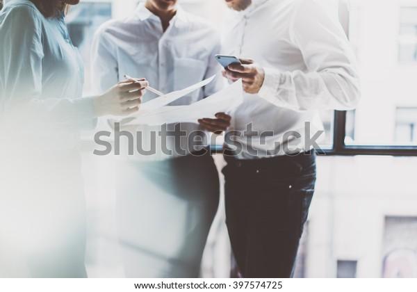 Business-Team-Meeting, Arbeitsprozess.Foto professionelle Crew arbeitet mit neuen Start-Projekt.Projektmanager in der Nähe von window.Analyse der Geschäftspläne, Smartphone-Hände. unscharf, Filmeffekt.Horizontal