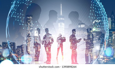 Business team members standing over night city background with double exposure of planet hologram. Concept of international company and globalization. Toned image
