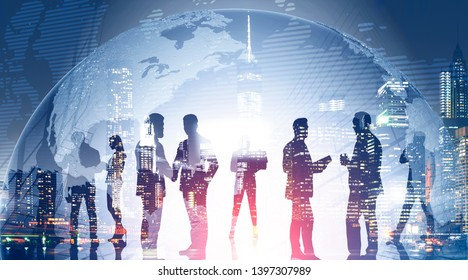 Business team members standing over night city background with double exposure of planet. Concept of international company and globalization. Toned image. Elements of this image furnished by NASA