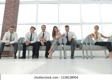 business team with mobile phones sitting in the lobby of the office