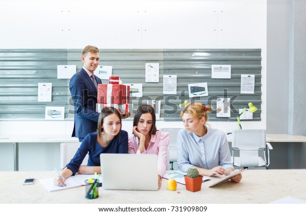 Business team in a modern bright office interior at work on a laptop.