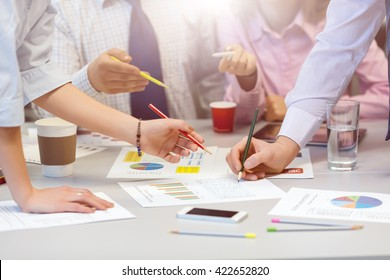 Business Team networking Concept - grey Office Table with many printed professional Paper Charts and Hands of young People discussing gesturing pointing with color pencils