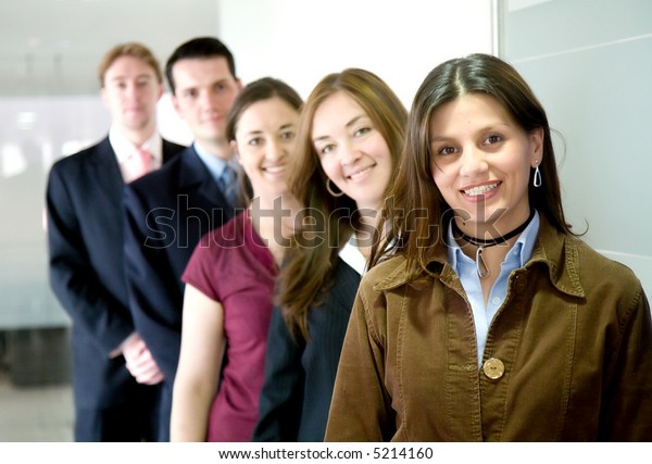 business team in an office all smiling and standing in a row