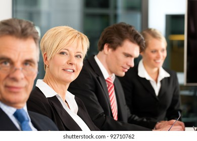 Business - team in an office; the boss is looking into the camera