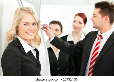 Business - team in an office, a colleague is standing in front of the flipchart, one female colleague is looking in to the camera