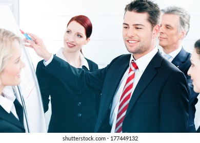Business - team in an office, a colleague is standing in front of the flipchart