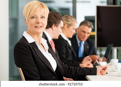 Business - team in an office; the female boss is looking into the camera