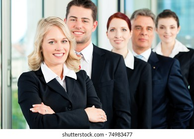 Business - team in an office; five colleagues or professionals in a row