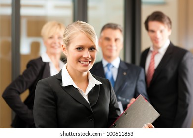 Business - team in an office, the junior manager is standing in front