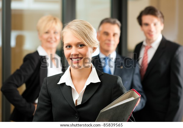 Business - team in an office; the junior manager is standing in front