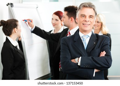 Business - team in an office, the senior executive is standing in front