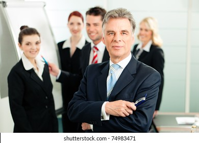 Business - team in an office; the senior executive is standing in front