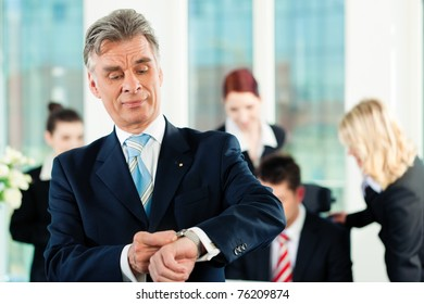 Business - team in an office; the senior executive is checking his watch to hold the deadline