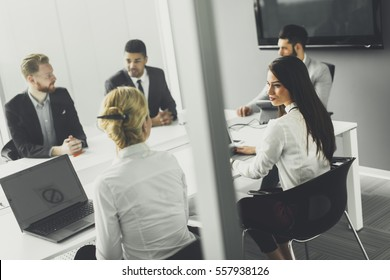 Business team on meeting in modern bright office interior and working on laptop