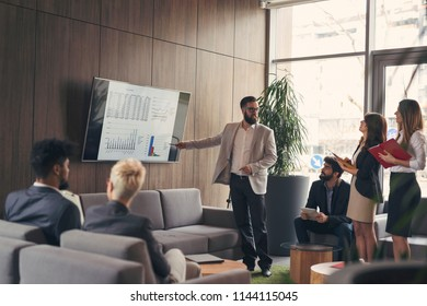 Business team on a morning briefing; business meeting and presentation in a modern office. Focus on the man leading the meeting