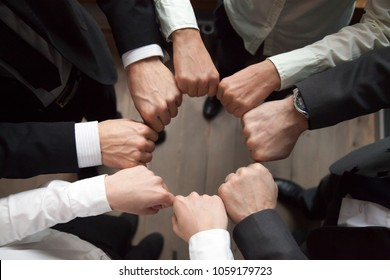 Business team or partners put fists in circle as concept of motivating engaging teambuilding activity, reliable support, help in cooperation, trust unity in collaboration teamwork, close up top view