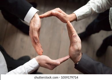 Business team people join hands forming circle, business protection, unity in care and support, shared corporate responsibility, help in teamwork, synergy trust safety concept, close up top view