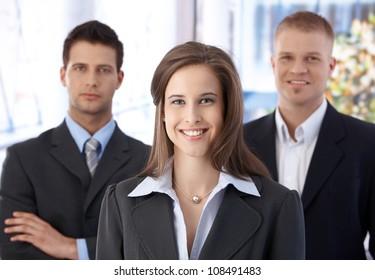 Business team portrait, happy confident businesswoman in focus, businessmen in background.