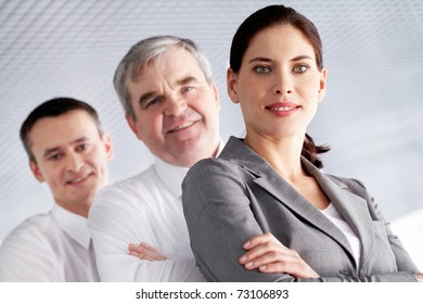 A business team with pretty leader in front looking at camera and smiling