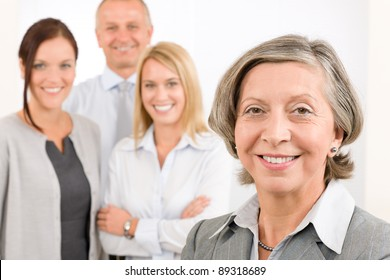 Business team senior businesswoman with attractive happy colleagues in office