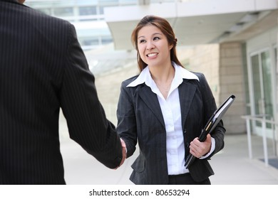 An business team shaking hands at office building