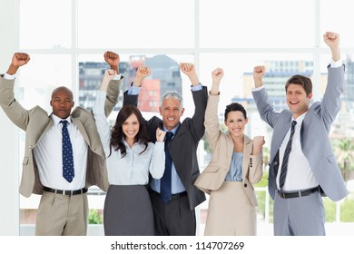 Business team smiling and standing upright with arms raised in success