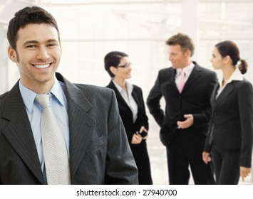 Business team standing in office lobby. Happy businessman in front, smiling and looking at camera, others talking in the background.