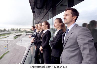 Business team standing on balcony of office building