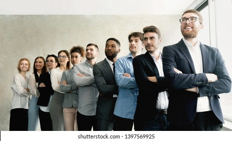 Business team standing in row with boss headed, looking aside in office