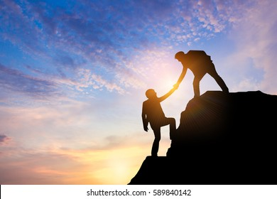 Business team success concept.silhouette of business man on peak mountain climbing helping on sunset background teamwork