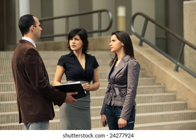 Business team of talking with client about a deal outdoors in front of an office building on stairs in the city