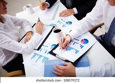Business team of three analyzing statistical data