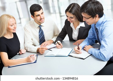 A business team of three plan work in office