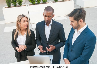 Business team of three watching and discussing content on laptop. Two men and woman standing outdoors, using computer and talking. Corporate meeting outside concept