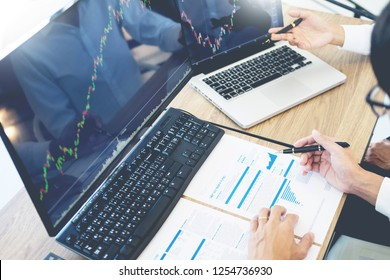 Business team trading Finance Stock Exchange analysis graph on multiple computer screens in modern trading office, financial and investment concept.