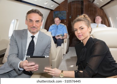 business team traveling in corporate jet and discussing a presentation