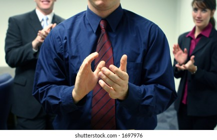 Business team of two men and one woman facing forward and clapping