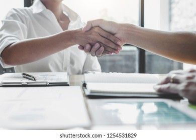 Business team two shaking hands after a meeting to sign agreement and become partner in the office, contract between their firms.
