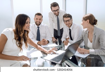 business team uses a laptop to check the results of their work