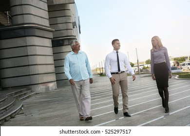 Business team walking and having conversation against business building.