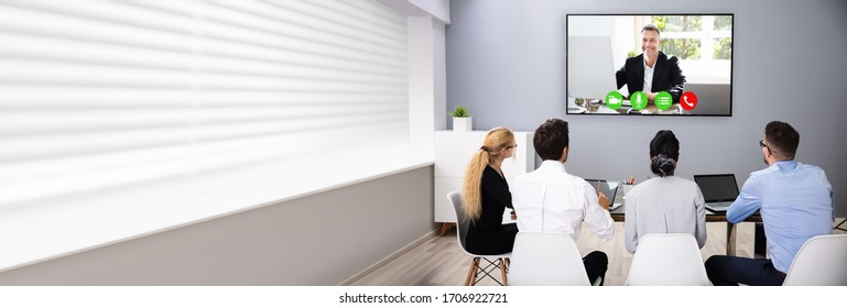 Business Team Watching Video Conference Call On TV