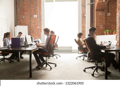 Business team women men workers working on computers in modern big coworking enterprise space, busy staff diverse professional employees office people group sitting at desks using pc at workplace