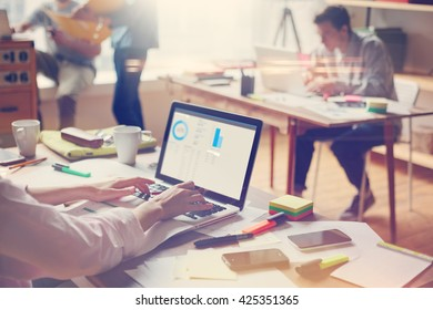 Business team at work. Open space office, laptops and paperwork. Film effect and lens flare effect, blurry background
