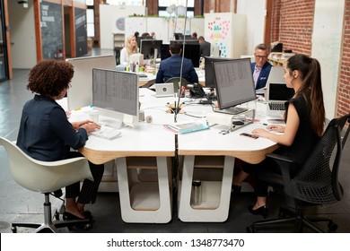 Business Team Working At Desks In Modern Open Plan Office