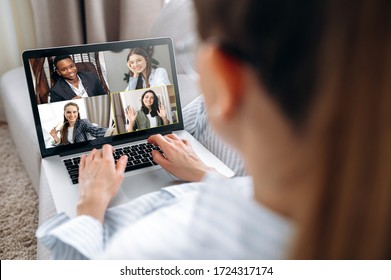 Business team working from home in a video conference. The back view of a girl who communicates online by video conference with her work colleagues using a laptop