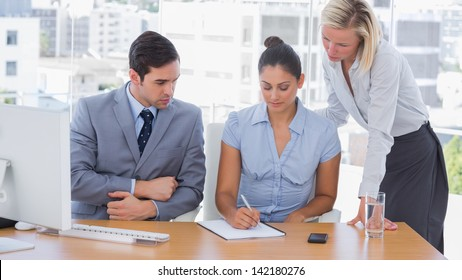 Business team working with a notepad at desk in office