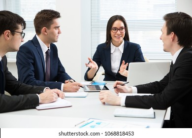Business team working in an office sitting around a table
